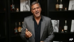 FILE - Actor George Clooney poses for photographs on arrival at the book launch of Cindy Crawford and his own Tequila launch, at the Beaumont Hotel in central London, Oct. 1, 2015.