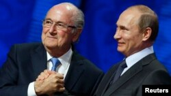 FIFA's President Sepp Blatter shakes hands with Russia's President Vladimir Putin (R) during the preliminary draw for the 2018 FIFA World Cup at Konstantin Palace in St. Petersburg, July 25, 2015.