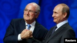 FILE - Now suspended FIFA President Sepp Blatter (L) shakes hands with Russian President Vladimir Putin during the preliminary draw for the 2018 FIFA World Cup at Konstantin Palace in St. Petersburg, July 25, 2015.