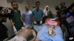 Libyan doctors stand near bodies of a man and a baby found in the damaged residential building in Tripoli's outskirts, Libya, on Sunday, June 19, 2011. Libyan officials claimed that the building was hit by a NATO airstrike. NATO continued to strike target
