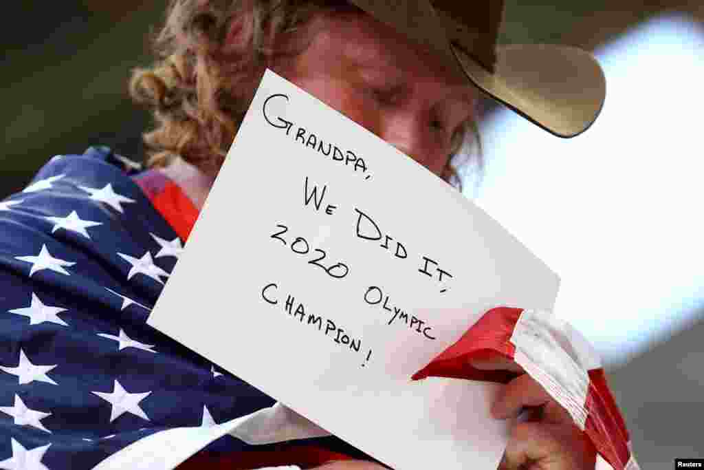 Ryan Crouser of the United States holds a message for his grandfather after winning the gold medal in the men's shot put final at the Tokyo 2020 Olympics.