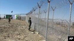 پاک افغان سرحد پر نصب کی جانے والی آہنی باڑ کے قریب ایک سیکیورٹٰی اہل کار سرحد پار کا جائزہ لے رہا ہے۔ فائل فوٹو
