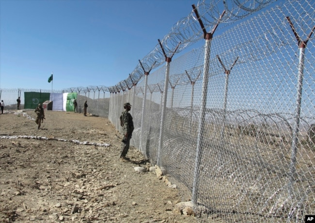 FILE - Pakistani soldiers stand guard at a fence between Pakistan and Afghanistan at Angore Adda, Pakistan, Oct. 18, 2017. Pakistan's military says the fencing and guard posts along the border with Afghanistan help prevent militant attacks.