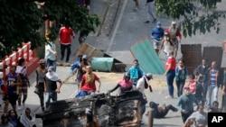 Los manifestantes antigubernamentales se enfrentan a las fuerzas de seguridad cuando muestran su apoyo a un aparente motín por parte de una unidad de la Guardia Nacional en el barrio de Cotiza en Caracas, Venezuela.