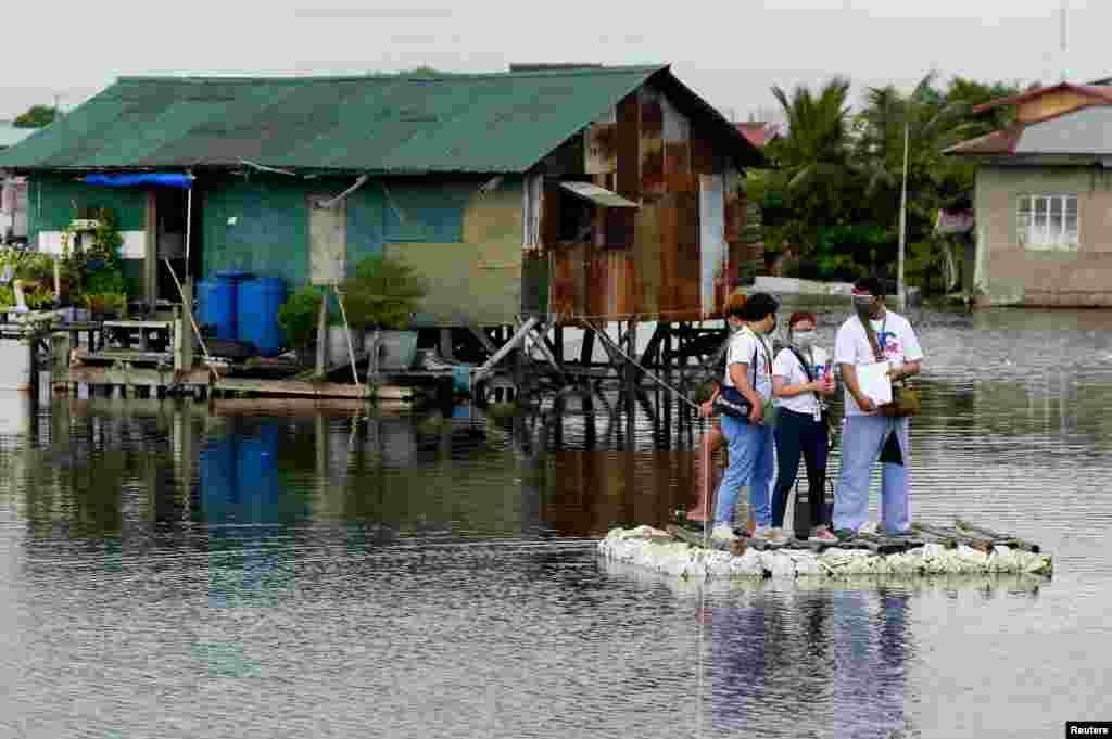 Suv bosgan ko'chalarda to'shakka mixlangan fuqarolarni koronavirusga qarshi emlash uchun kelayotgan tibbiyot xodimlari. Filippin.