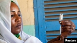 Une femme prépare un vaccin au Darfour, le 8 octobre 2012.