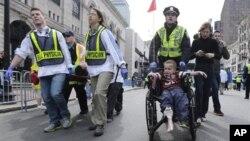 Cảnh sát và nhân viên y tế đưa người bị thương ra khỏi hiện trường sau vụ nổ bom ở Boston, ngày 15/4/2013.
