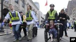 Polisi dan petugas medis membawa para korban luka akibat ledakan bom di Boston (15/4). (Foto: AP)
