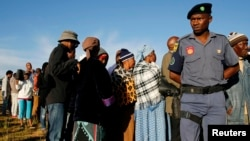 FILE - A police officer looks on at a voting station during the Lesotho national election in Magkhoakhoeng village outside the capital Maseru , Feb. 28, 2015.