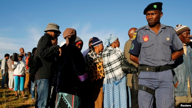 File - A police officer looks on at a voting station during the Lesotho national election in Magkhoakhoeng village outside the capital Maseru, Feb. 28, 2015.