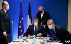 Presiden Prancis Emmanuel Macron (tengah) diapit oleh Perdana Menteri Prancis Jean Castex (kiri) dan Sekretaris Jenderal Istana Elysee Alexis Kohler (kanan) memulai pertemuan keamanan nasional untuk membahas spyware Pegasus. (Foto: AFP)