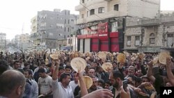 In this citizen journalism image made on a mobile phone, taken Tuesday, May 3, 2011, Syrian men carry pieces of bread during a protest against Syrian President Bashar Assad's regime, in the coastal town of Banias