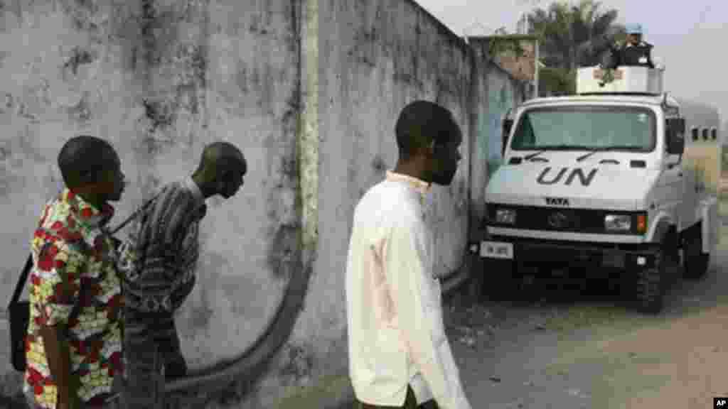 Des manifestants se cachent à l'arrière d'in véhicule de l'ONU alors que la police tire et lance des gaz lacrymogènes lors d'une manifestation, lundi 10 Janvier, 2005. . (AP Photo / John Bompengo)
