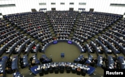 FILE - Members of the European Parliament take part in a voting session in Strasbourg, France, April 5, 2017.