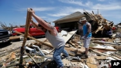 Workers clear damage from Oklahoma tornado.
