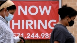 FILE - Women walk past by a 'Now Hiring' sign outside a store in Arlington, Virginia, Aug. 16, 2021..