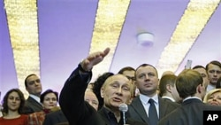Russian Prime Minister and presidential candidate Vladimir Putin, center, greets his supporters at his election headquarters in Krasnoyarsk, Russia, Monday, March 5, 2012. (AP Photo/Alexander Zemlianichenko)