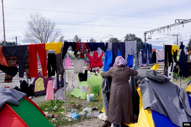 FILE - Refugees try to dry their belongings after a downpour at the Idomeni camp in Greece, March 2016. (J. Dettmer/VOA)