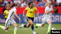 Colombia forward Lady Andrade (16) moves the ball against United States defender Becky Sauerbrunn (4) and defender Julie Johnston (19) during the second half in the round of sixteen in the FIFA 2015 women's World Cup soccer tournament at Commonwealth Stad