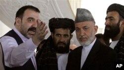 ປະທານາທິບໍດີອັຟການິສຖານ ທ່ານ Hamid Karzai (ສອງຈາກຂວາ) ພົບປະກັບນ້ອງຊາຍຂອງທ່ານ ທ່ານ Ahmad Wali Karzai (ຊ້າຍ) ທີ່ເມືອງ Argandab ໃນແຂວງການດາຮາ (9 ຕຸລາ 2010)