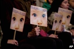 """Warga menggenggam plakat bergambar bayi bertuliskan """"Kembali(kan) ke Anak-anak"""" dalam bahasa Spanyol, di luar pengadilan Buenos Aires, Argentina (5/7)."""