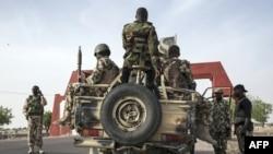 Des soldats de la 7e division de l'armée nigériane se préparent à quitter Maiduguri dans un convoi lourdement armé sur la route de Damboa dans l'Etat de Borno, au nord-est du Nigeria, le 25 mars 2016.