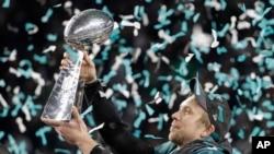 Jwè ekip Philadelphia Eagles, Nick Foles, ki leve trofe Vince Lombardi a anlè apre viktwa ekip la sou New England Patriots dimanch 4 fevriye 2018 la. (Foto: AP/Chris O'Meara).