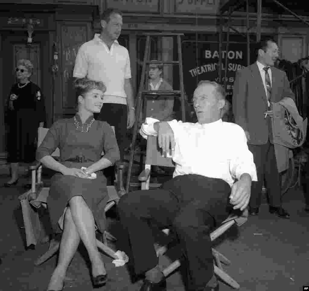 """Relaxing between scenes, Bing Crosby talks with Debbie Reynolds on the Hollywood set of """"Say One for Me"""" in Los Angeles, Dec. 29, 1958. They co-star with Robert Wagner in the film."""