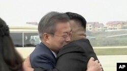 Lidè 2 Kore yo te bay akolad apre Prezidan sid-koreyen an, Moon Jae-in (a goch) te fin debake nan ayewopò emntènasyonal Sunan nan Pyongyang.