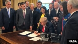 President Donald Trump, center, signs the NASA Transition Authorization Act of 2017, alongside members of the Senate, Congress, and National Aeronautics and Space Administration in the Oval Office of the White House in Washington, Tuesday, March 21, 2017.