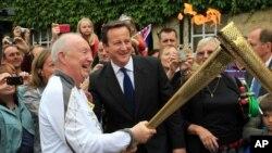 """El primer ministro británico David Cameron con el portador de la llama olímica Clive Stone, en Woodstock. Cameron se disculpo por el """"error"""" de confundir la bandera de Corea del Norte."""