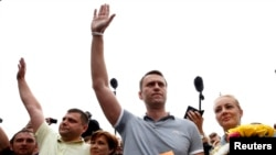 Russian protest leader Alexei Navalny (2nd R) and his co-defendant Pyotr Ofitserov (2nd L), stand near their wives, surrounded by supporters and journalists, after arriving from Kirov at a railway station in Moscow, July 20, 2013.