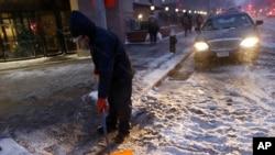 Seorang pekerja membersihkan salju di jalanan di rumah sakit Brooklyn's Methodist di New York (26/1).