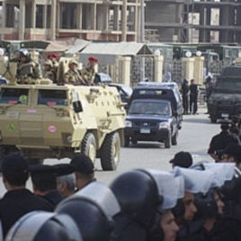 Egyptian policemen line the street as an armored army vehicle guards a convoy carrying former Egyptian interior minister Habib el-Adly and his aides, as they arrive at the court in Cairo, May 21, 2011