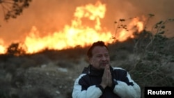 A man prays during an early-morning Creek Fire that broke out in the Kagel Canyon area in the San Fernando Valley north of Los Angeles, in Sylmar, California, Dec. 5, 2017. (REUTERS/Gene Blevins )