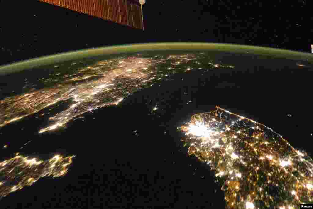 Photo taken by the Expedition 38 crew aboard the International Space Station (ISS) on January 30, 2014 shows the night view of the Korean Peninsula, and North Korea in the middle is almost completely dark compared to neighboring South Korea (bottom right) and China (top left).
