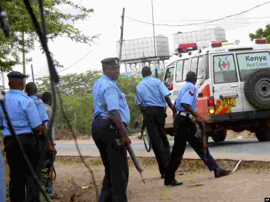 Kenyan police officers take positions during an attack by gunmen outside the Garissa University College as an ambulance carrying the injured are taken to the hospital, in Garissa, April 2, 2015.