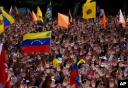 Anti-government protesters hold their hands up during the symbolic swearing-in of Juan Guaido, head of the opposition-run National Assembly, who declared himself interim president of Venezuela, during a rally demanding President Nicolas Maduro's resignation, in Caracas, Venezuela, Jan. 23, 2019.