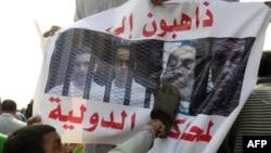 Một ngườii dùng chiếc giày đập vào hình của cựu Tổng thống Mubarak và hình các con ông treo trước học viện cảnh sát ở Cairo nơi diễn ra phiên tòa hôm 5/9/11