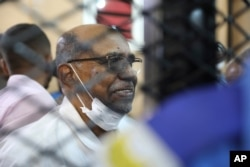 FILE - Sudan's ousted president Omar al-Bashir sits at the defendant's cage during his trial, at a courthouse in Khartoum, Sudan, Sept. 15, 2020.