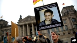 지난해 11월 독일 베를린 의사당 건물 앞에서 미국 정보기관의 도청에 항의하는 시위대가 도청 사실을 폭로한 에드워드 스노든의 사진을 들고 있다.