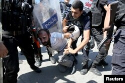 FILE - Riot police detain a demonstrator during a protest against the suspension of teachers from classrooms over alleged links with Kurdish militants, in the southeastern city of Diyarbakir, Turkey, Sept. 9, 2016.