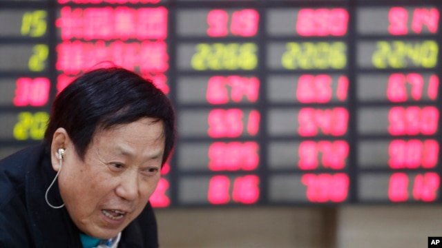 An investor talks in front of the stock price monitor at a private securities company in Shanghai, China, Nov. 25, 2013. (AP)