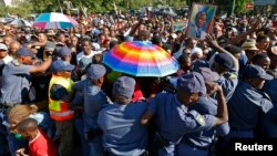 South African police try to block mourners at a checkpoint while they attempt to walk to the Union building to see the body of former South African President Nelson Mandela, in Pretoria, Dec. 13, 2013.