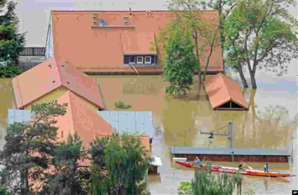 Người dân di chuyển bằng xuồng từ nhà này sang nhà khác khi sông Elbe dâng nước gây ngập lụt ở thành phố Dresden, miền đông nước Ðức, vào thứ Năm ngày 6/6/2013. (AP Photo/Jens Meyer)