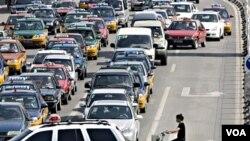 Seorang pengendara sepeda di Beijing menembus kemacetan lalu-lintas. Jumlah kendaraan pribadi meningkat lebih cepat dibanding kapasitas jalan raya di Tiongkok.