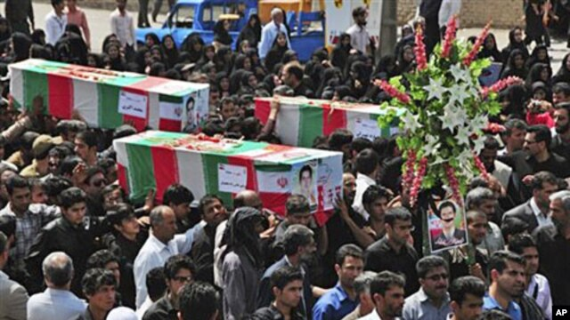 During a funeral ceremony, people carry flag-draped coffins of victims of two bomb blasts in Zahedan,  southeast of Tehran, claimed by the Sunni group, Jundallah, 17 Jul 2010