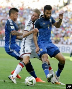 Germany's Christoph Kramer gets hit in the face by Argentina's Ezequiel Garay shoulder (2) while pinned between Garay and Marcos Rojo during the World Cup final soccer match.