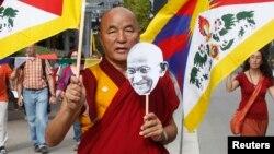 Seorang biarawan Budha dengan membawa bendera Tibet melakukan protes kebijakan China di Barcelona, Spanyol (foto: dok). Seorang biarawan di Tibet melakukan aksi protes dengan membakar diri, Senin (11/11).