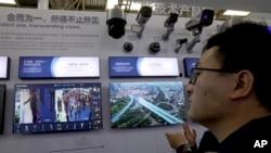 在北京举行的2018中国安全博览会上,一名男子在显示器上查看来自监控设备制造商海康威视的技术(10月23日)。